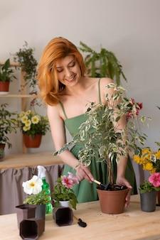 Mulher sorridente de tiro médio com planta