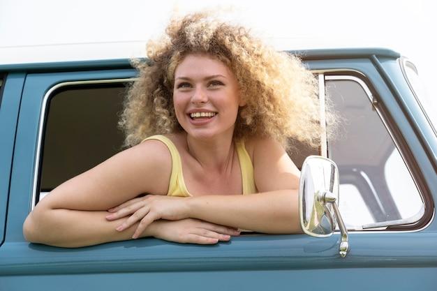 Mulher sorridente de tiro médio com van