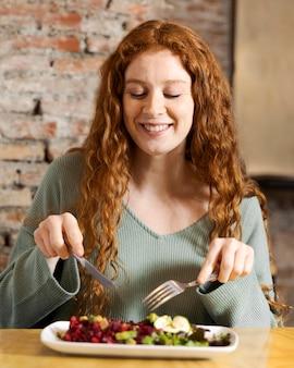 Mulher sorridente de tiro médio comendo