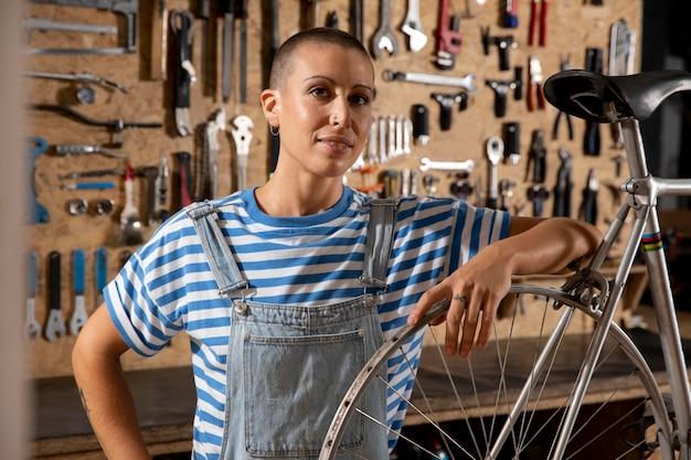 Mulher sorridente de tiro médio consertando bicicleta
