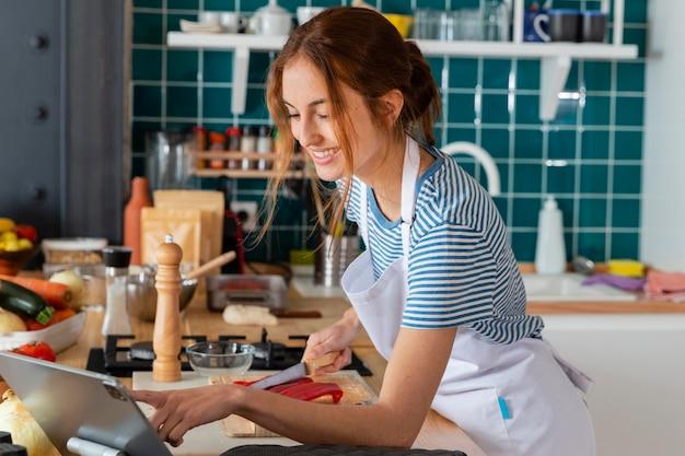 Mulher sorridente de tiro médio cortando pimenta