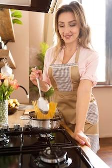 Mulher sorridente de tiro médio cozinhando no fogão Foto Premium