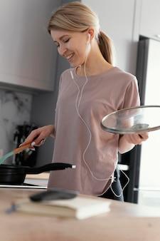 Mulher sorridente de tiro médio cozinhando