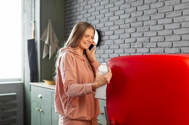 Mulher sorridente de tiro médio falando ao telefone