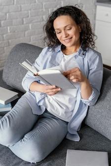 Mulher sorridente de tiro médio lendo