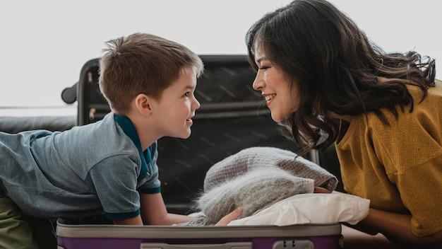 Mulher sorridente de tiro médio olhando para criança