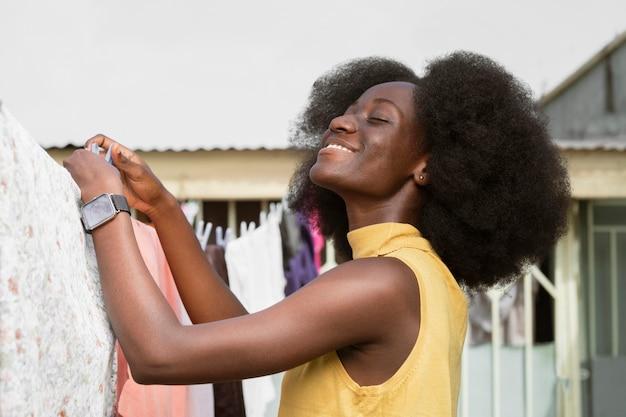 Mulher sorridente de tiro médio pendurando roupas para secar