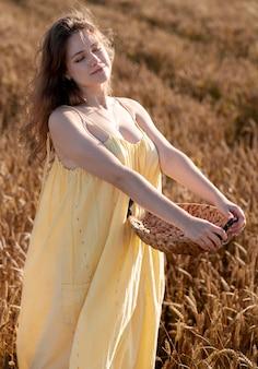 Mulher sorridente de tiro médio posando com uma cesta