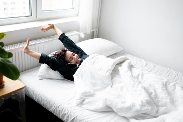 Mulher sorridente de tiro médio se espreguiçando na cama