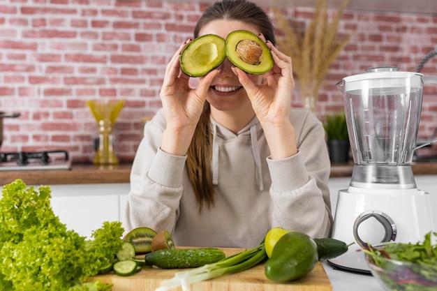 Mulher sorridente de tiro médio segurando abacate