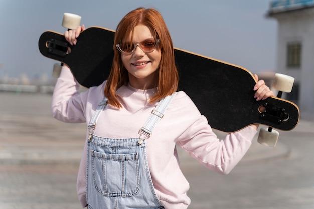 Mulher sorridente de tiro médio segurando longboard
