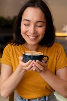 Mulher sorridente de tiro médio segurando uma xícara de café