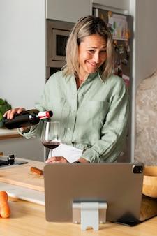 Mulher sorridente de tiro médio servindo vinho