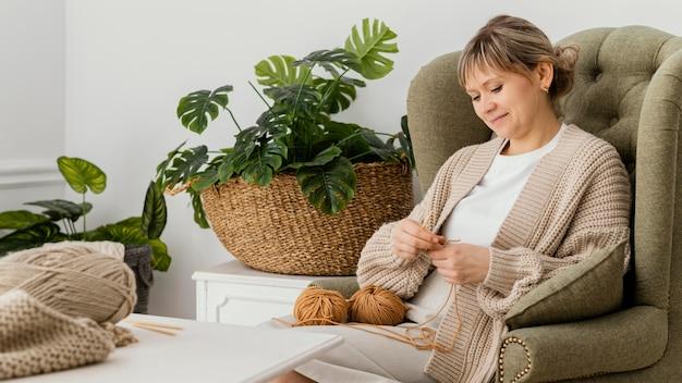 Mulher sorridente de tiro médio tricotando na poltrona