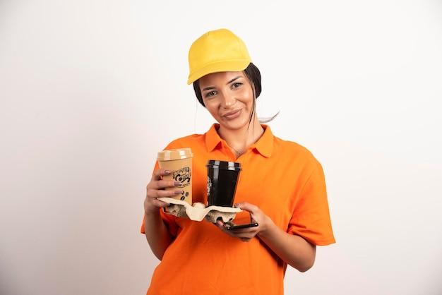 Mulher sorridente de uniforme segurando duas xícaras de café.