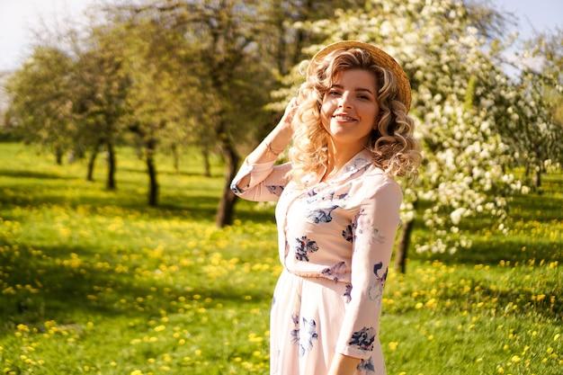 Mulher sorridente de verão com chapéu de palha no parque - jardim de maçãs em dia ensolarado de primavera