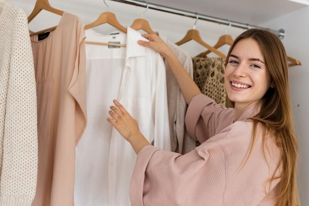 Mulher sorridente, decidindo o que vestir