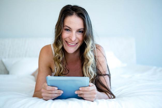 Mulher sorridente, deitada de bruços, na cama, rolando no tablet