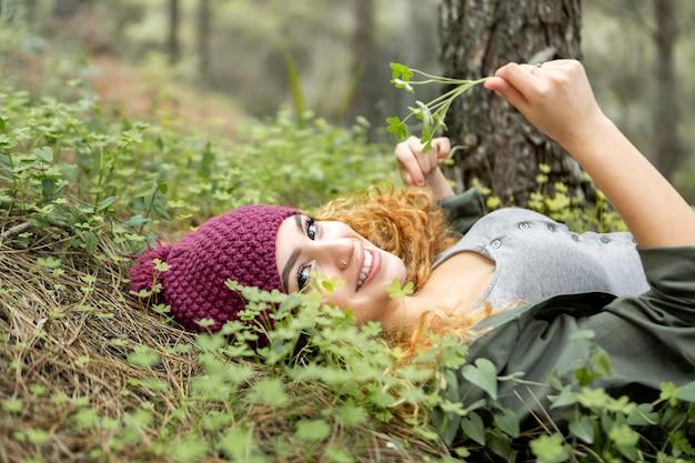 Mulher sorridente deitada na grama