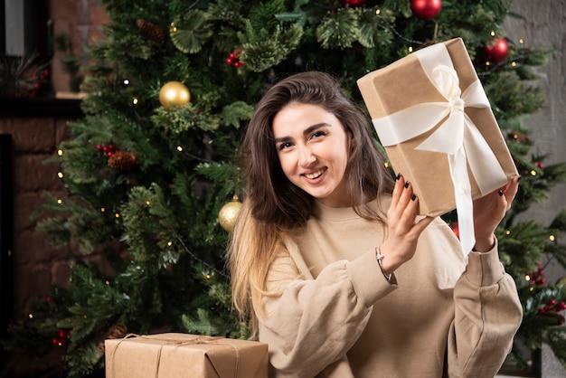 Mulher sorridente deitada no tapete fofo com presentes de natal.