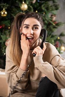Mulher sorridente deitada no tapete fofo, fazendo chamadas.