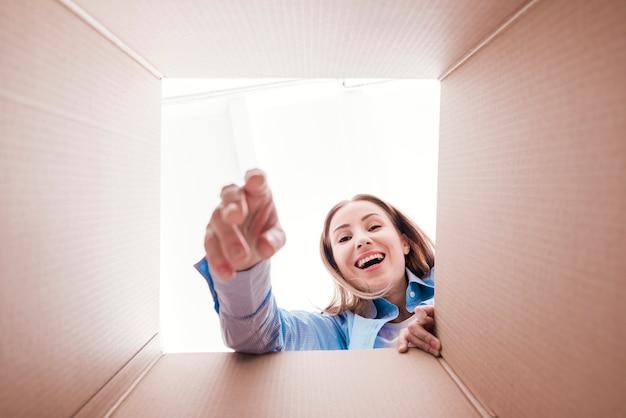 Mulher sorridente dentro da parte inferior da caixa