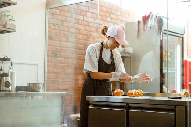 Mulher sorridente derrama açúcar de confeiteiro em pães frescos na mesa de uma padaria artesanal
