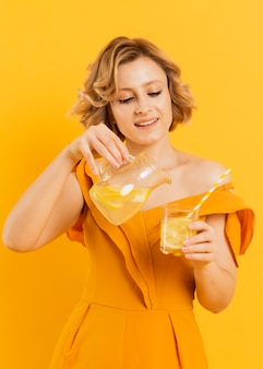 Mulher sorridente derramando limonada