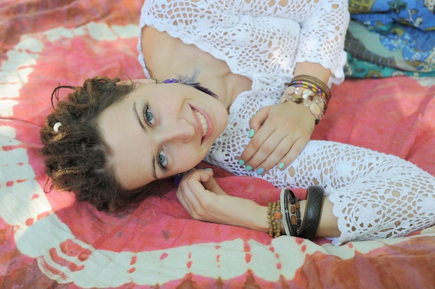Mulher sorridente descansando ao ar livre e deitada no tapete