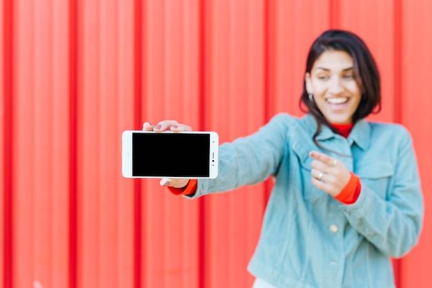 Mulher sorridente desfocada, mostrando o telefone celular