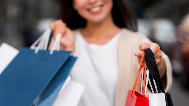 Mulher sorridente desfocada segurando sacolas de compras após a sessão de venda