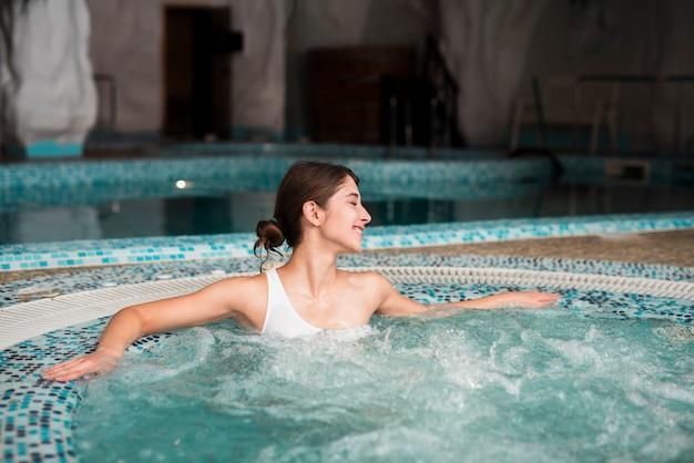 Mulher sorridente, desfrutando da banheira de hidromassagem no spa
