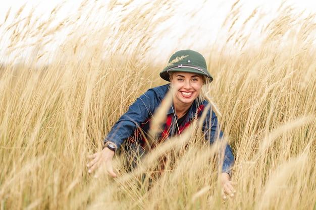 Mulher sorridente, desfrutando de trigo