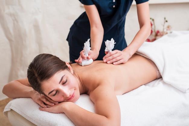 Mulher sorridente, desfrutando de uma massagem nas costas
