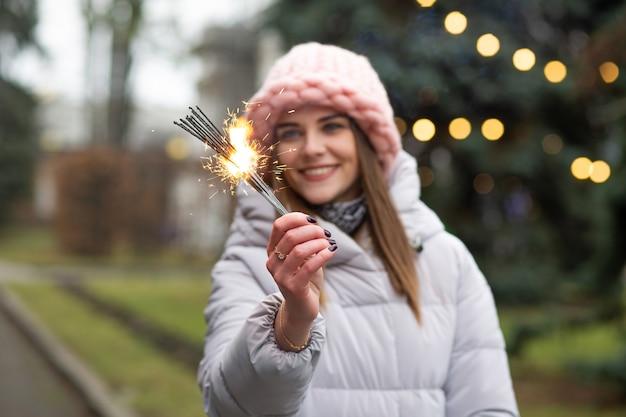 Mulher sorridente deslumbrante se divertindo com estrelinhas perto da árvore do ano novo