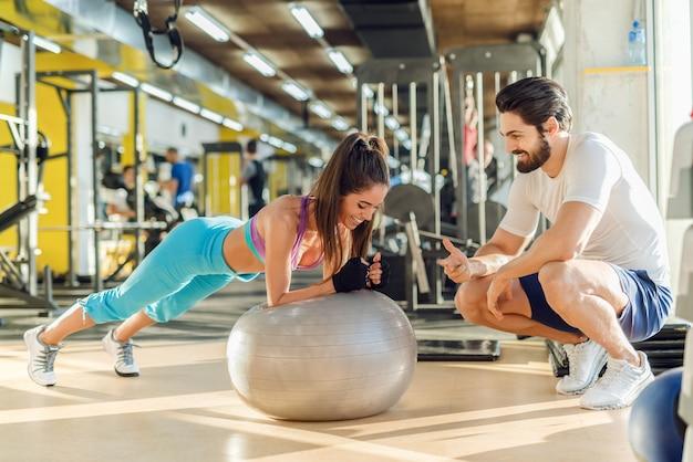Mulher sorridente desportiva fazendo pranchas na bola de pilates enquanto seu personal trainer agachado ao lado dela e torcendo por ela.