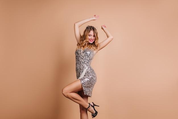Mulher sorridente despreocupada com roupa glamorosa dançando com as mãos ao alto na festa
