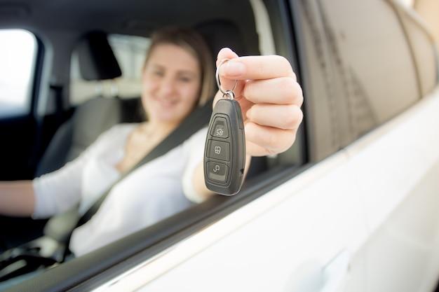 Mulher sorridente dirigindo um carro segurando as chaves do carro