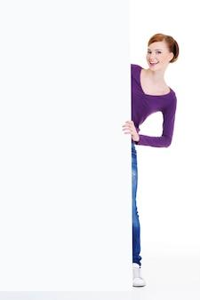Mulher sorridente divertida olha para fora por causa de um banner de publicidade
