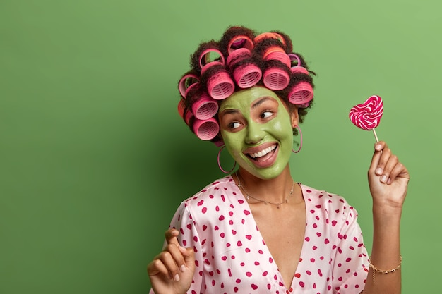 Mulher sorridente e alegre dança despreocupada, mexe-se com os braços erguidos, se diverte em casa, passa por procedimentos de beleza, aplica máscara facial para refrescar a pele, usa rolos de cabelo, segura pirulito delicioso