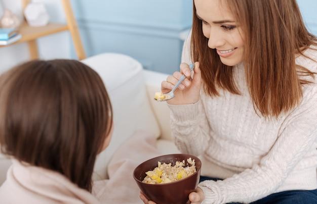 Mulher sorridente e alegre dando café da manhã para a filha enquanto está sentada no sofá