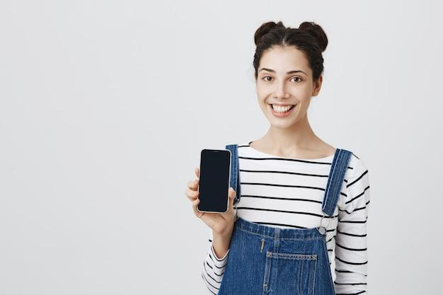Mulher sorridente e alegre mostrando aplicativo de smartphone na tela