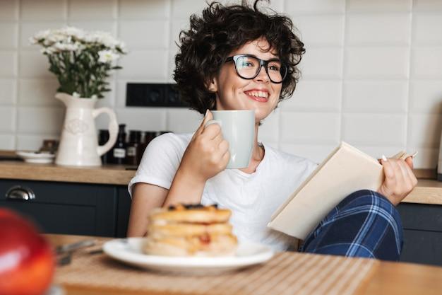 Mulher sorridente e alegre tomando um saboroso café da manhã enquanto está sentada na cozinha de casa, lendo um livro