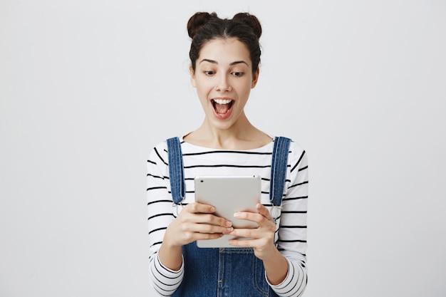 Mulher sorridente e animada olhando para um tablet digital