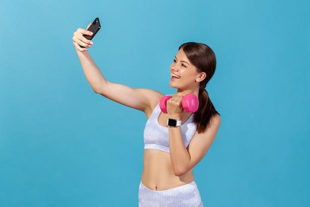 Mulher sorridente e atlética fazendo selfie para aumentar os músculos e malhar na academia