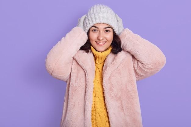 Mulher sorridente e atraente com cabelo escuro e suéter de malha branca