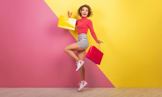 Mulher sorridente e atraente com roupa colorida elegante pulando com sacolas de compras