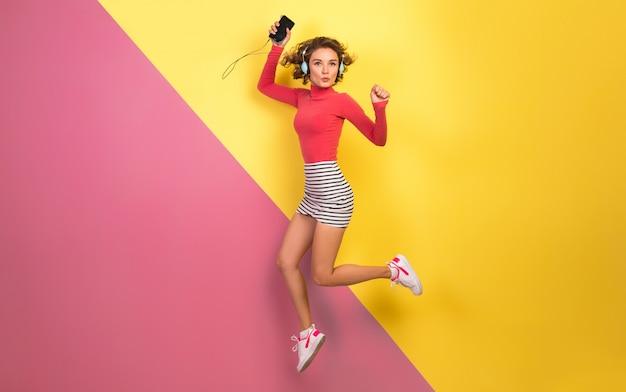 Mulher sorridente e atraente com roupa colorida elegante pulando e ouvindo música em fones de ouvido