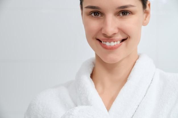 Mulher sorridente e atraente em um manto branco em pé no banheiro