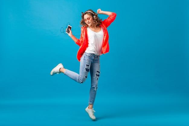 Mulher sorridente e atraente feliz dançando ouvindo música em fones de ouvido, vestida com roupa de estilo hipster isolada no fundo azul do estúdio, vestindo jaqueta rosa e óculos escuros